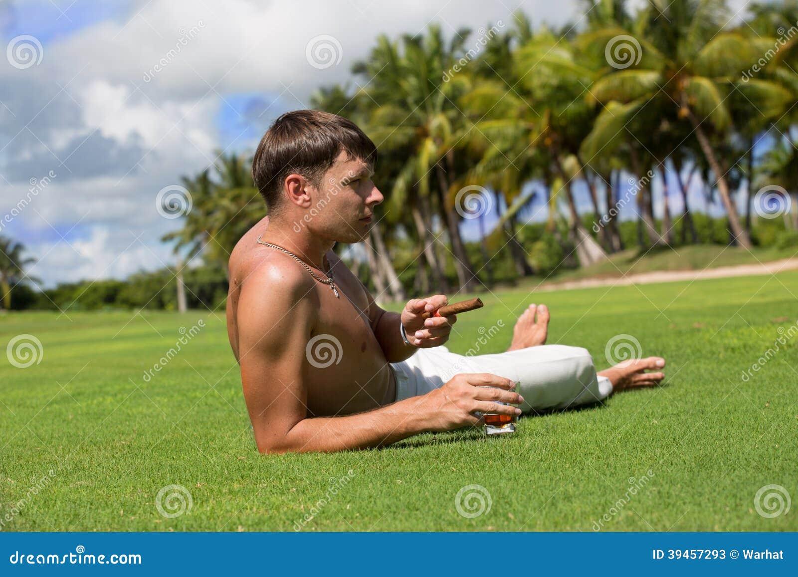 Mann liegt auf einem grünen Feld mit einem Glas Rum und Zigarren