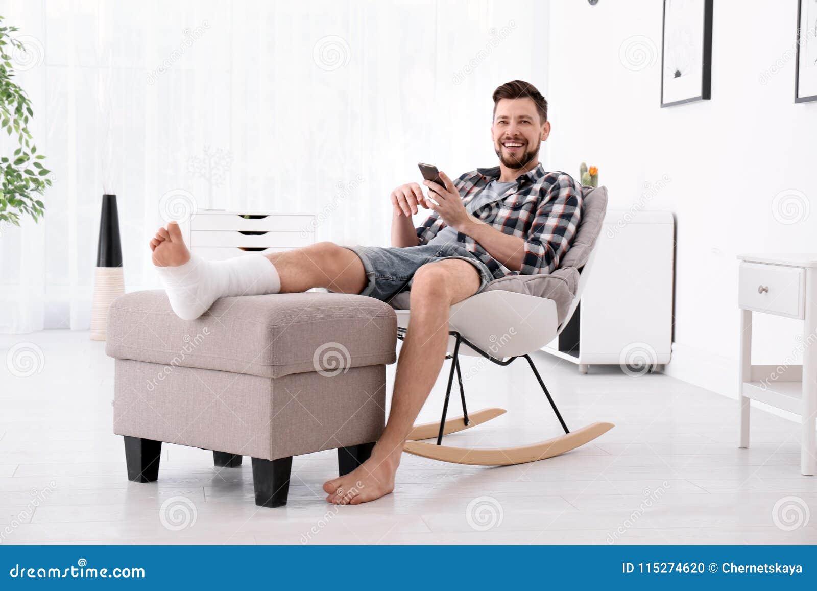 Mann mit dem gebrochenen Bein in der Form unter Verwendung des Handys