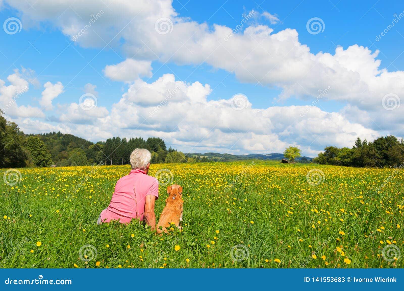 Mann mit dem Hund, der in der Landschaft sitzt
