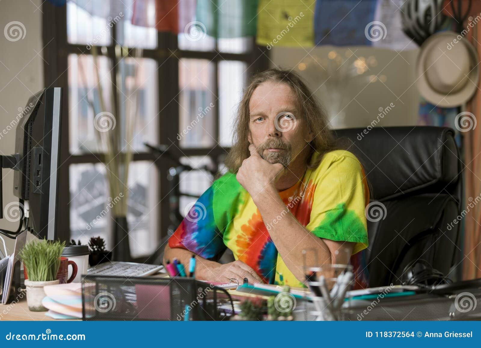 Mann mit dem langen Haar in einem bunten Büro