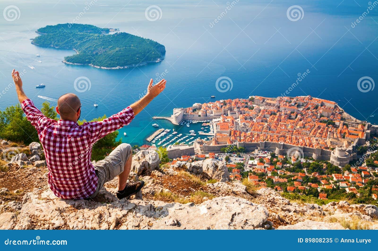 Mann mit den geöffneten Armen, die unten zur alten Stadt von Dubrovnik schauen