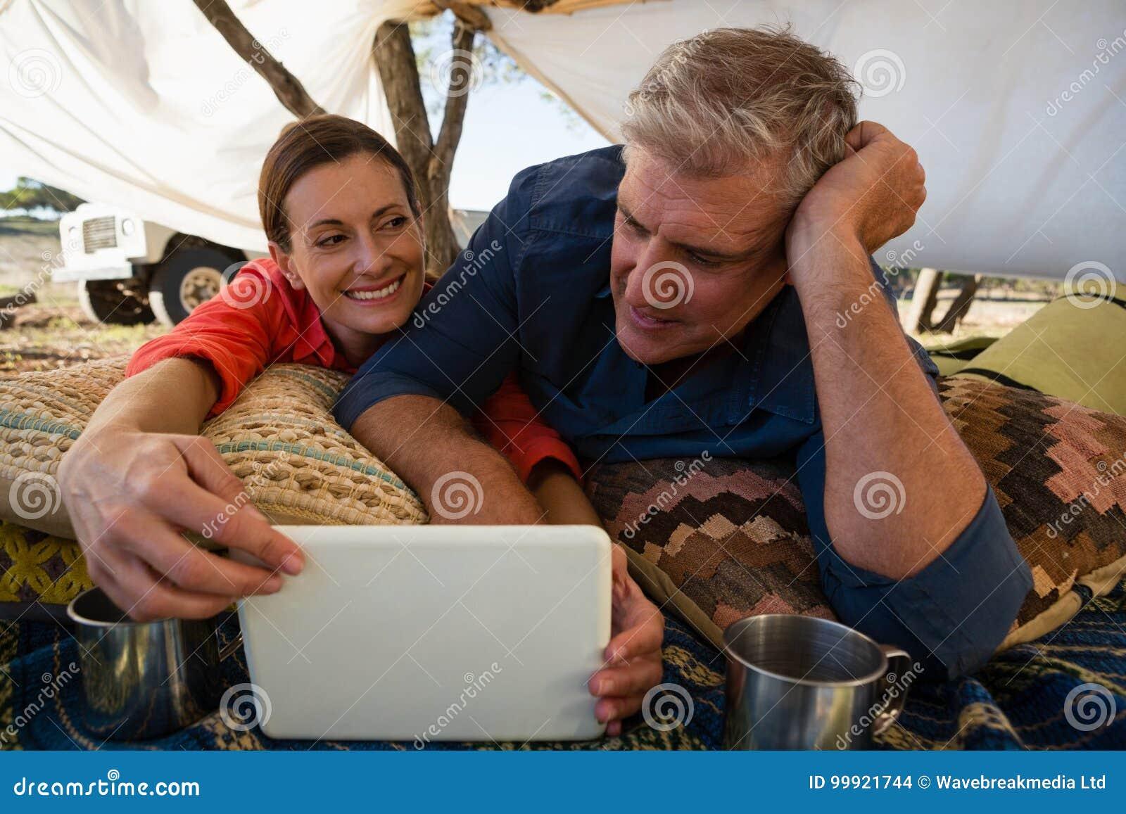 Mann mit der Frau, die Tablette im Zelt betrachtet