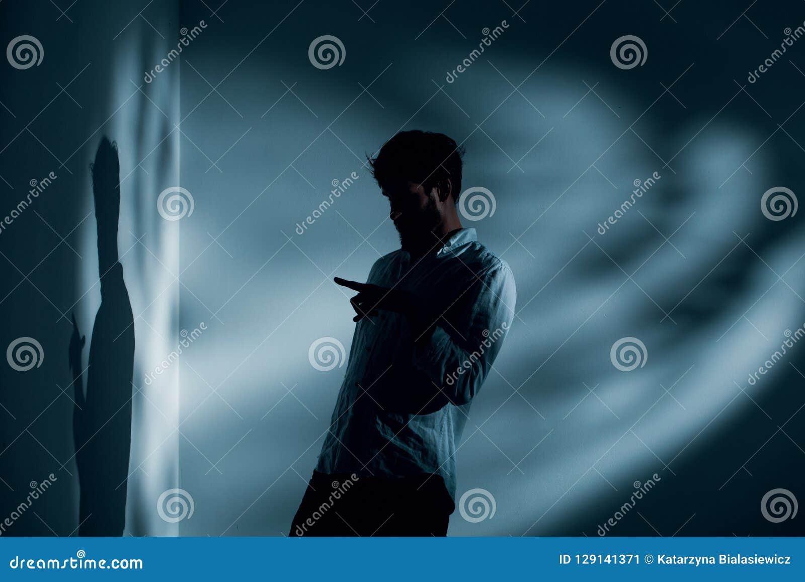 Mann mit der Schizophrenie, die allein im dunklen Innenraum sprechend mit seinem Schatten, Foto mit Kopienraum steht