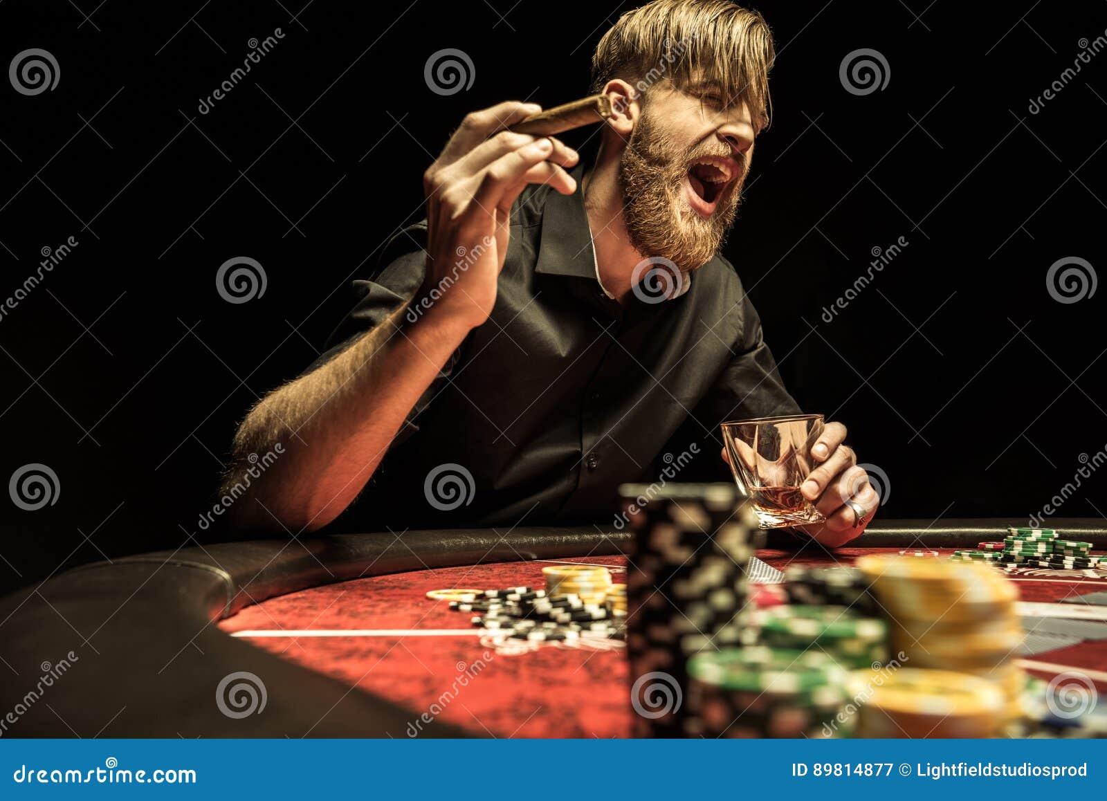 Mann mit der Zigarre und Glas, die am Pokertisch sitzen und schreien