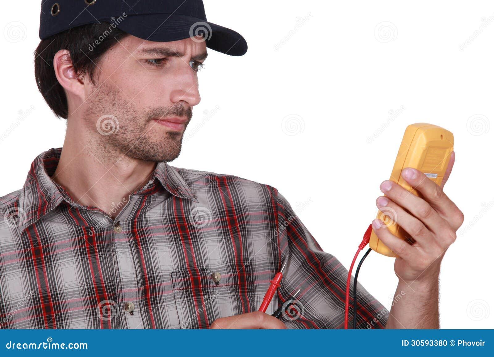 Mann mit einem Voltmeter