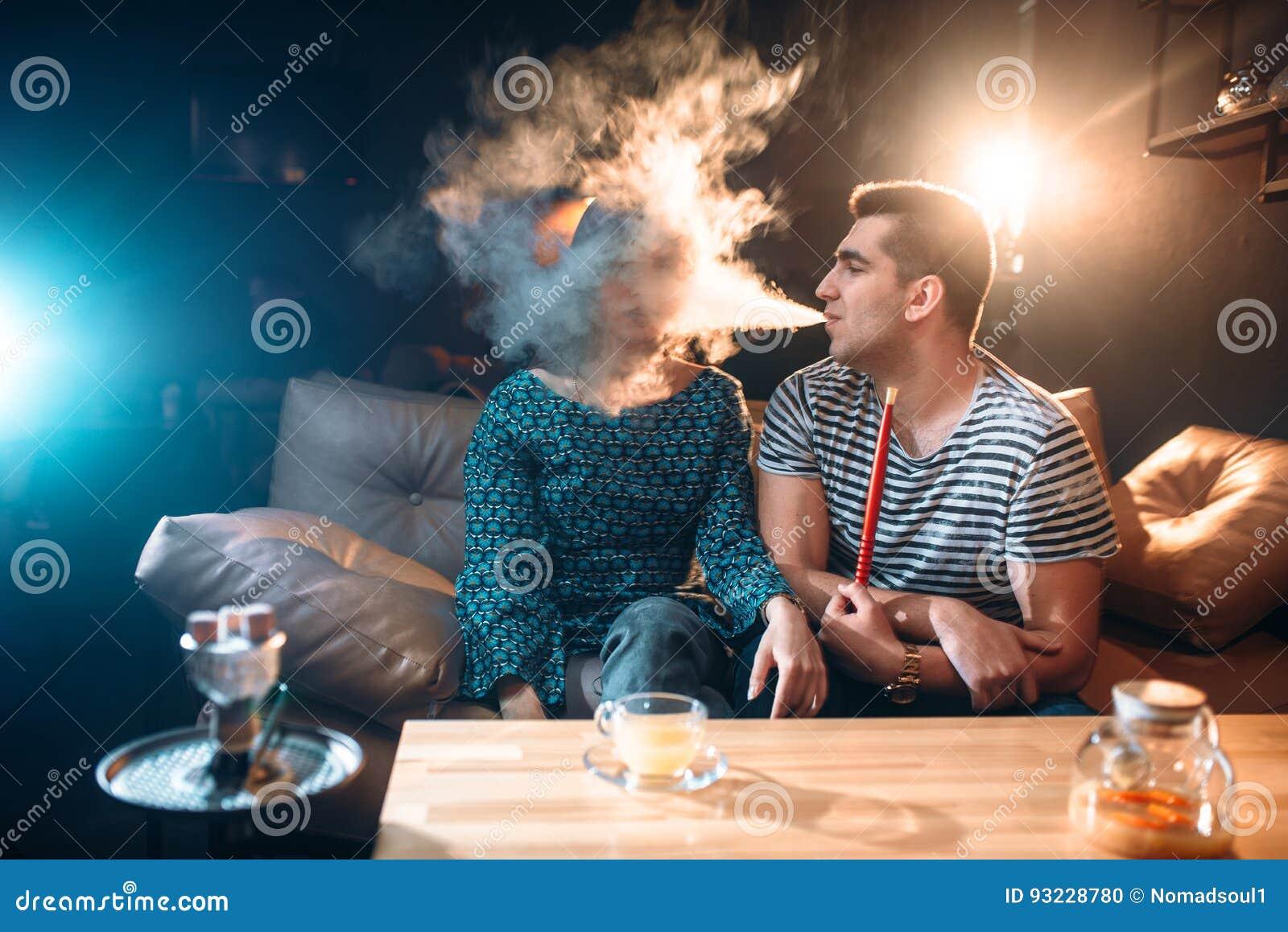 Mann mit Huka, Schläge rauchen im Gesicht der Frau