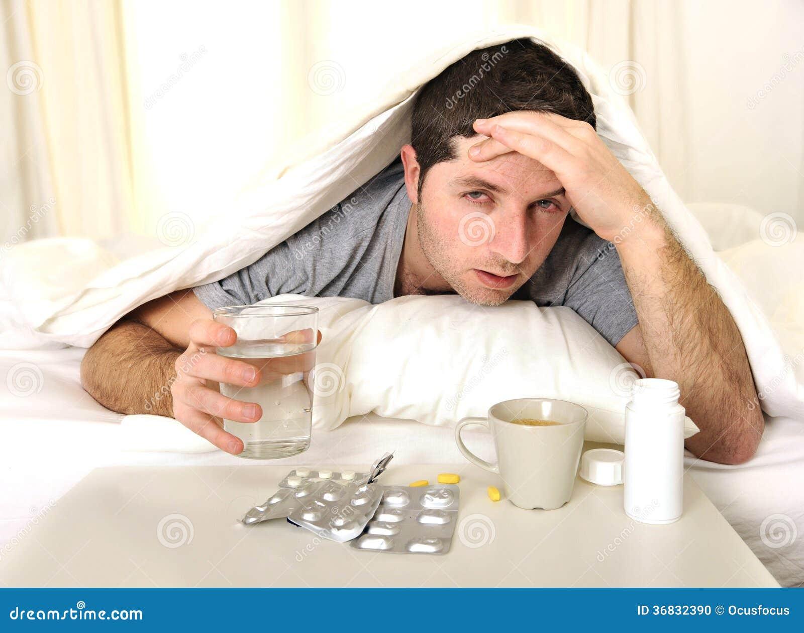 mann mit kopfschmerzen und kater im bett mit tabletten. Black Bedroom Furniture Sets. Home Design Ideas