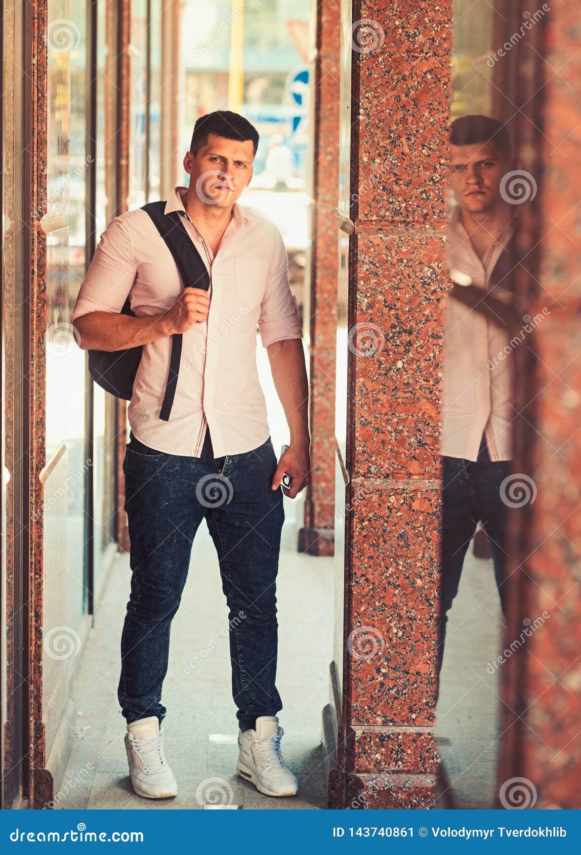 Mann mit Reisetasche auf sonnigem im Freien Macho auf moderne Hemd- und Jeansmode Art und Weisebaumuster auf Stra?e stattlich