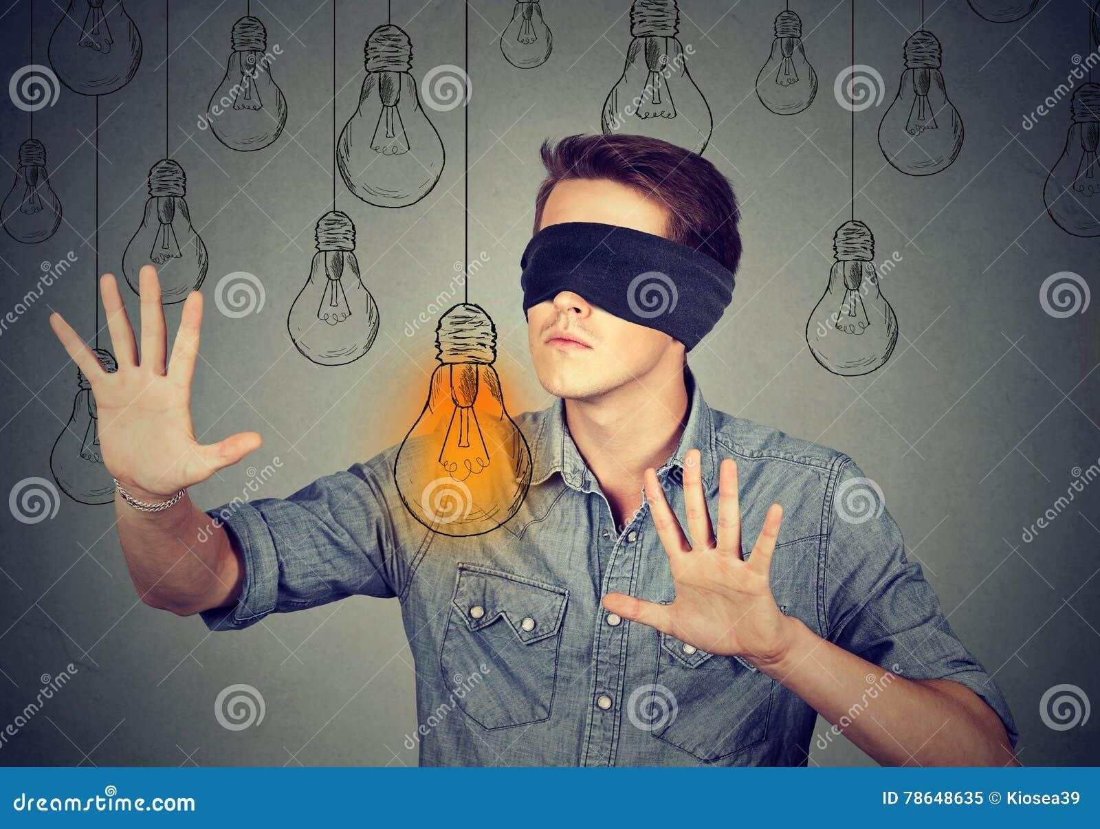 Mann mit verbundenen Augen, der durch die Glühlampen suchen nach Idee geht