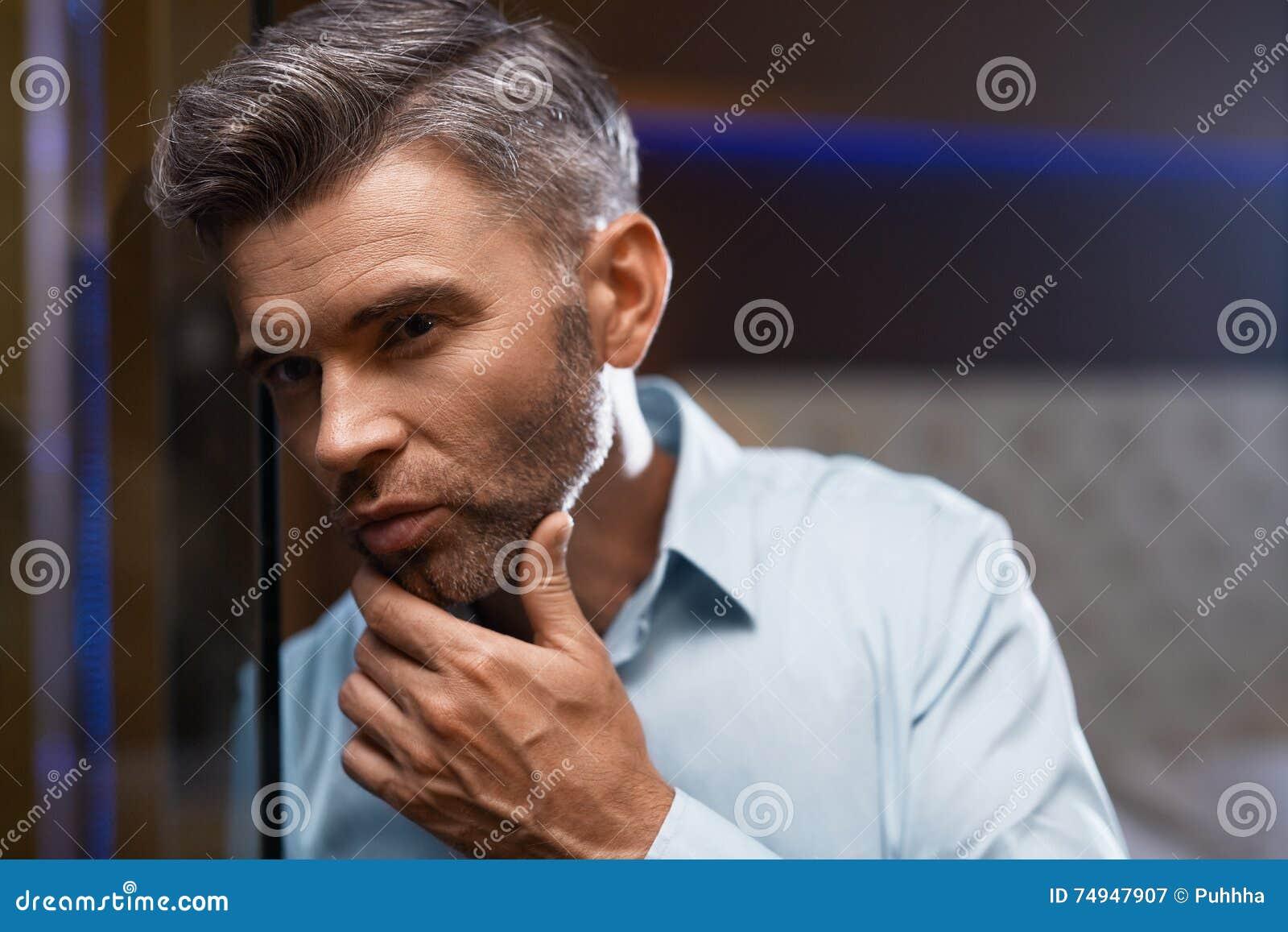 Mann-Pflegen Gut aussehender Mann mit Bart-rührendem Gesicht Zutreffen des transparenten Lacks