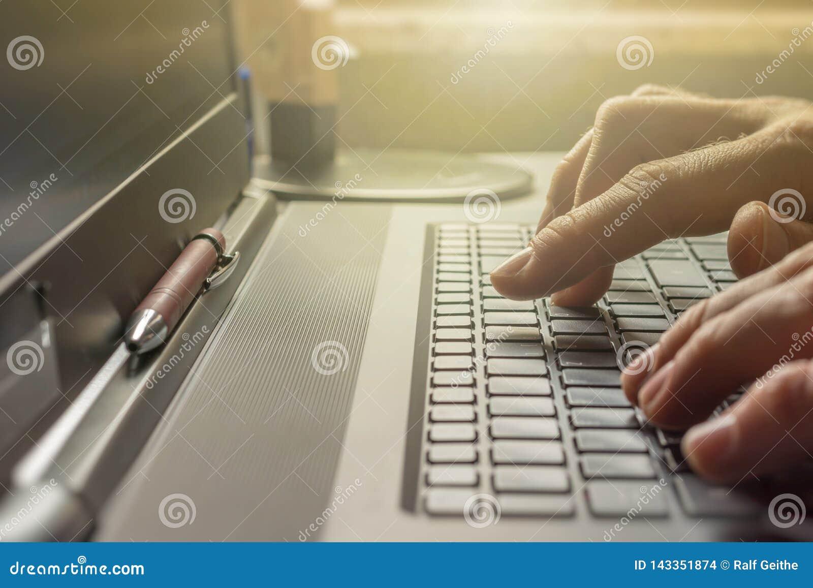 Mann schreibt auf der Tastatur seines Laptops im Büro