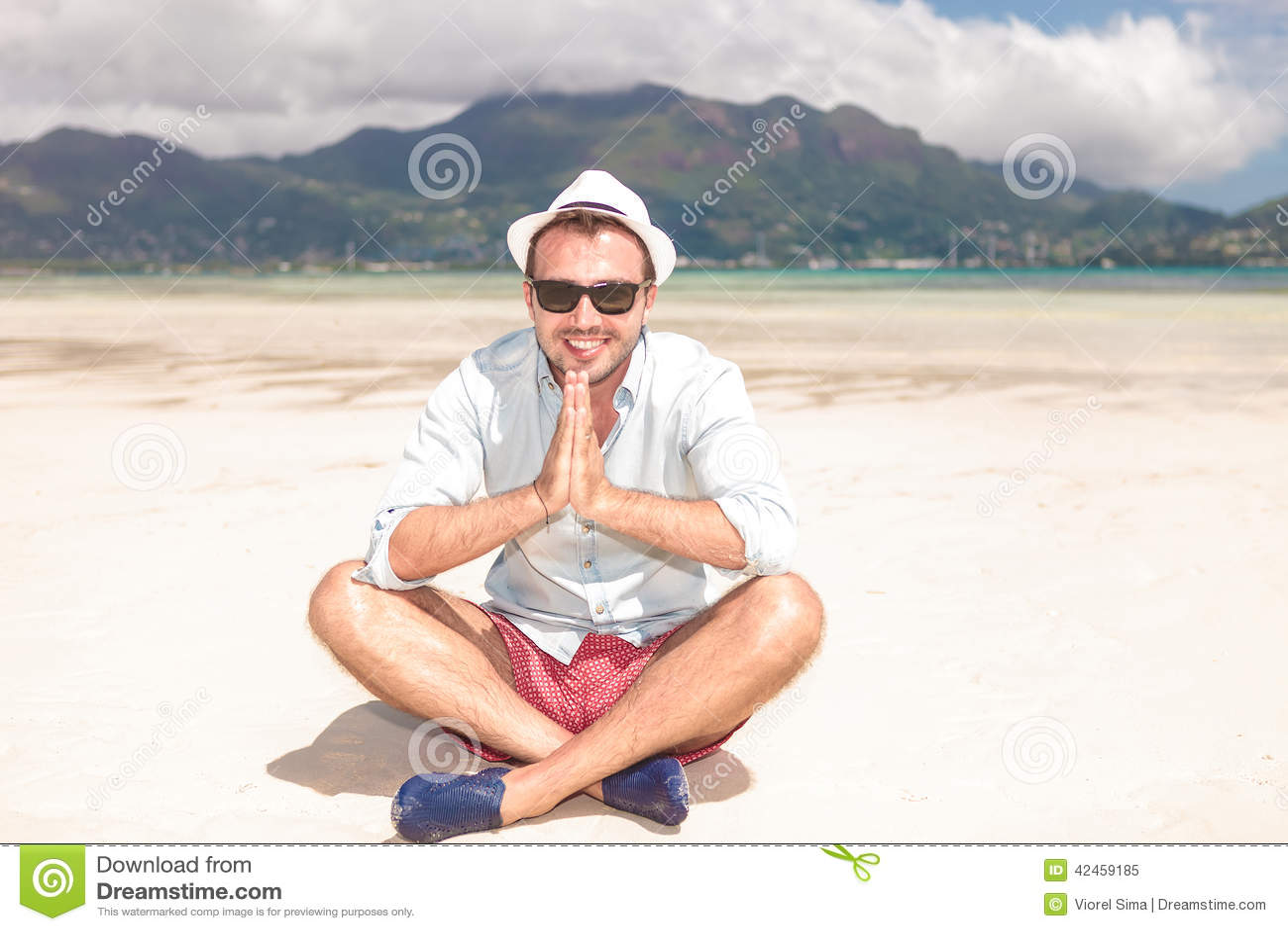 Mann sitzt auf dem Strand und betet
