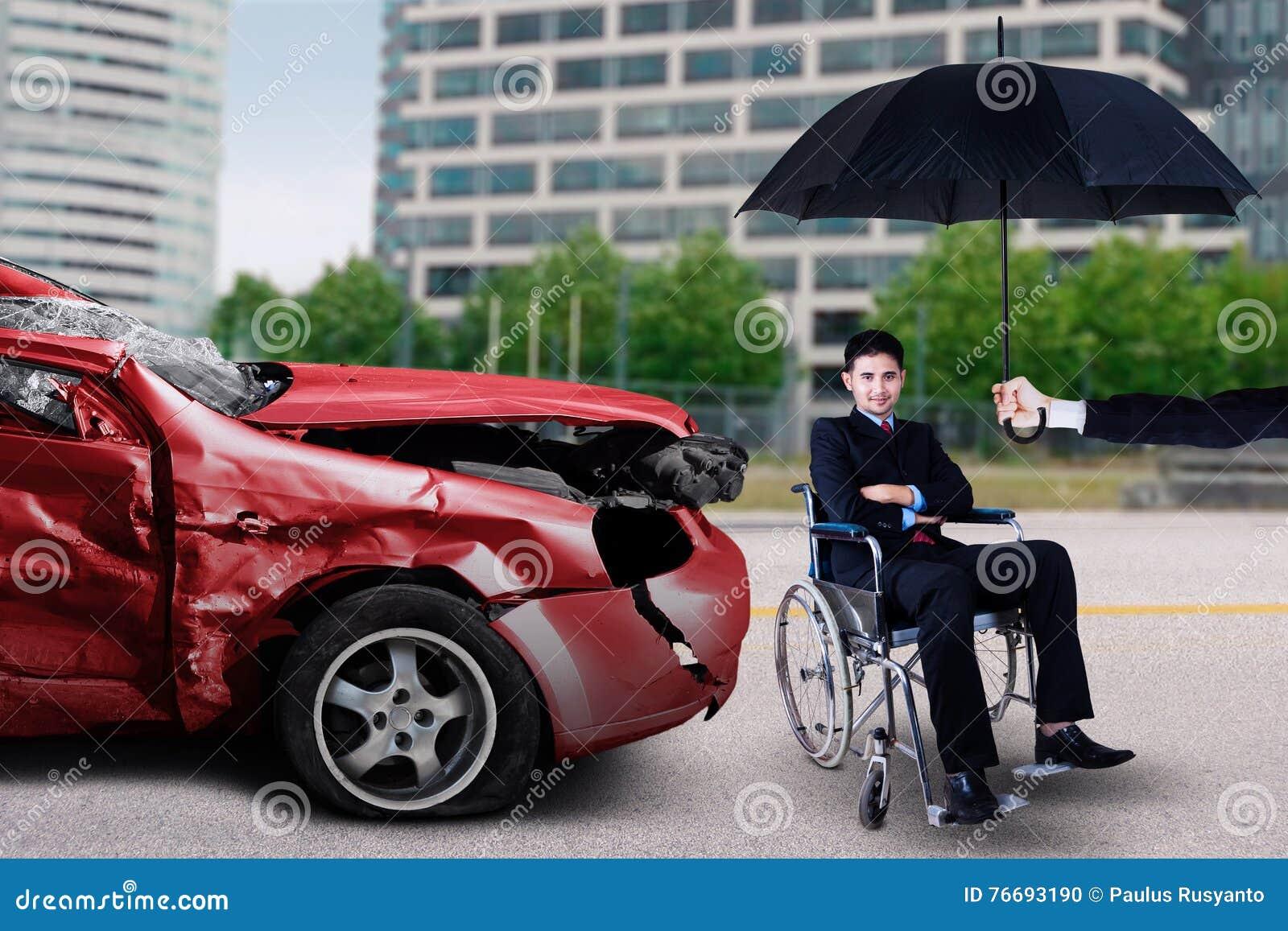 Mann sitzt auf Rollstuhl mit beschädigtem Fahrzeug