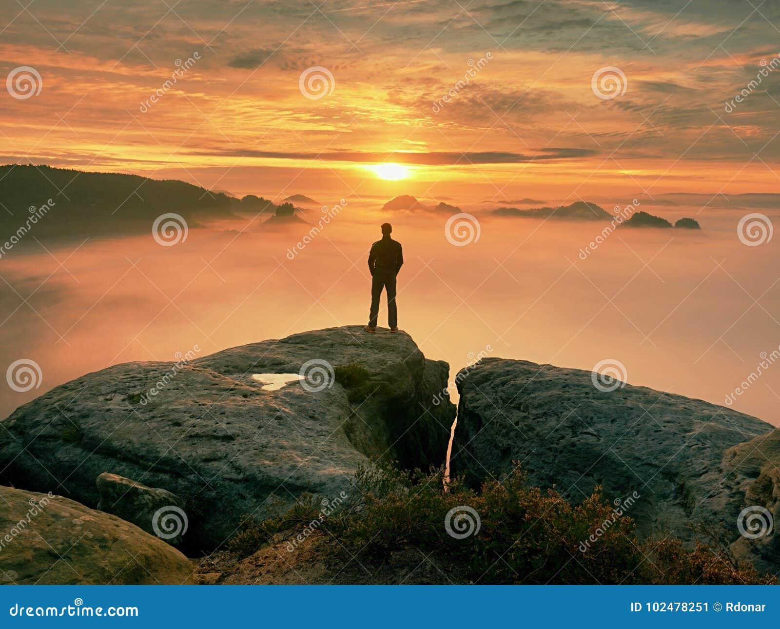 Mann steht allein auf der Spitze des Felsens Wanderer, der zum Herbst Sun am Horizont aufpasst Schöner Moment das Wunder der Natu