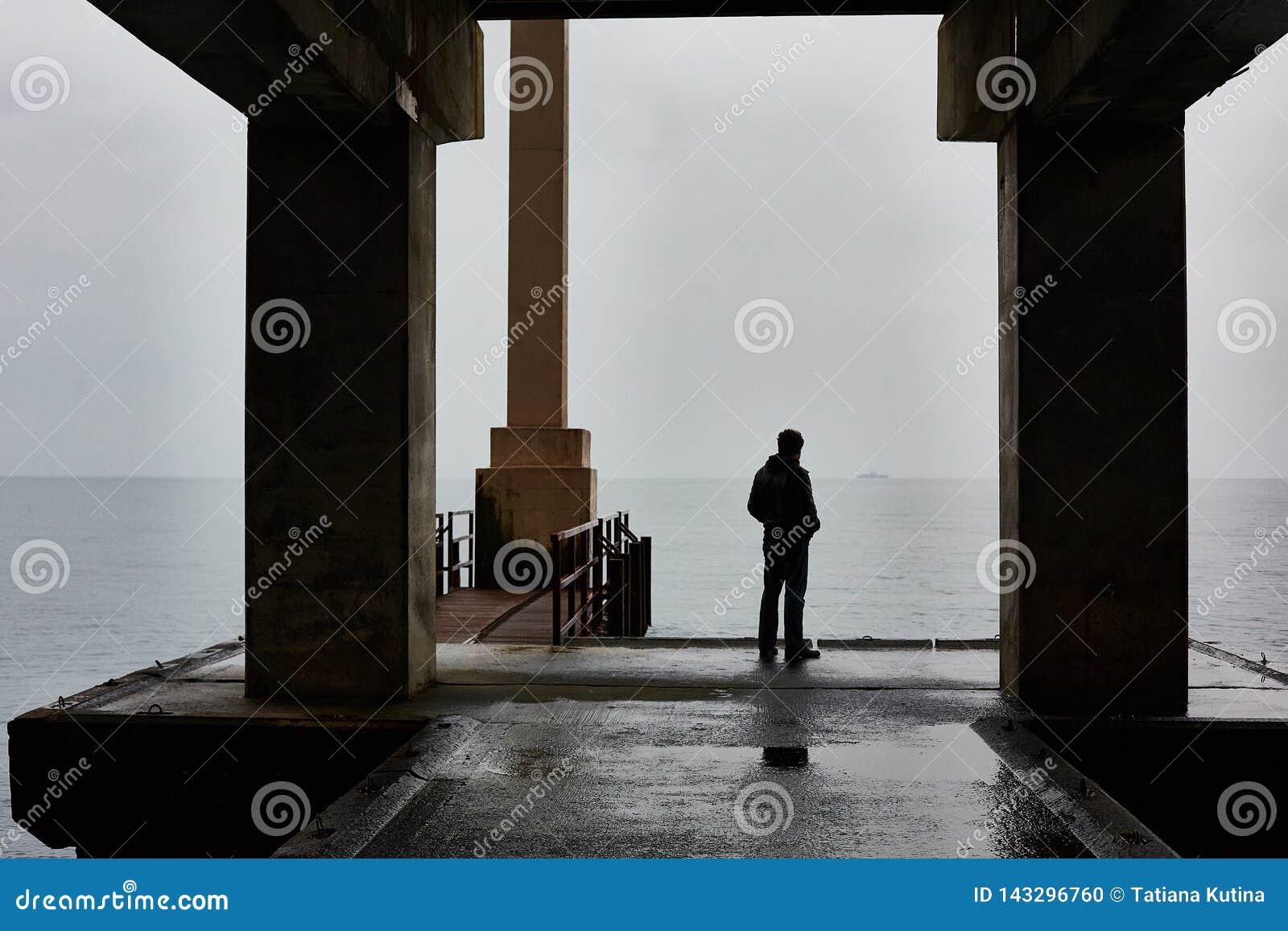 Mann steht auf einem Pier von Meer im schlechten Wetter allein Nebelige Luft