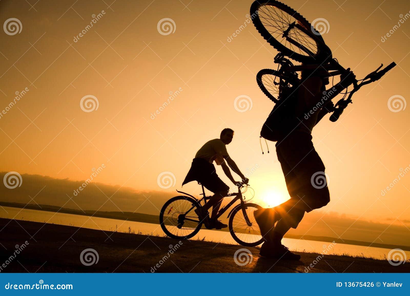 Mann trägt ein Fahrrad am Sonnenuntergang