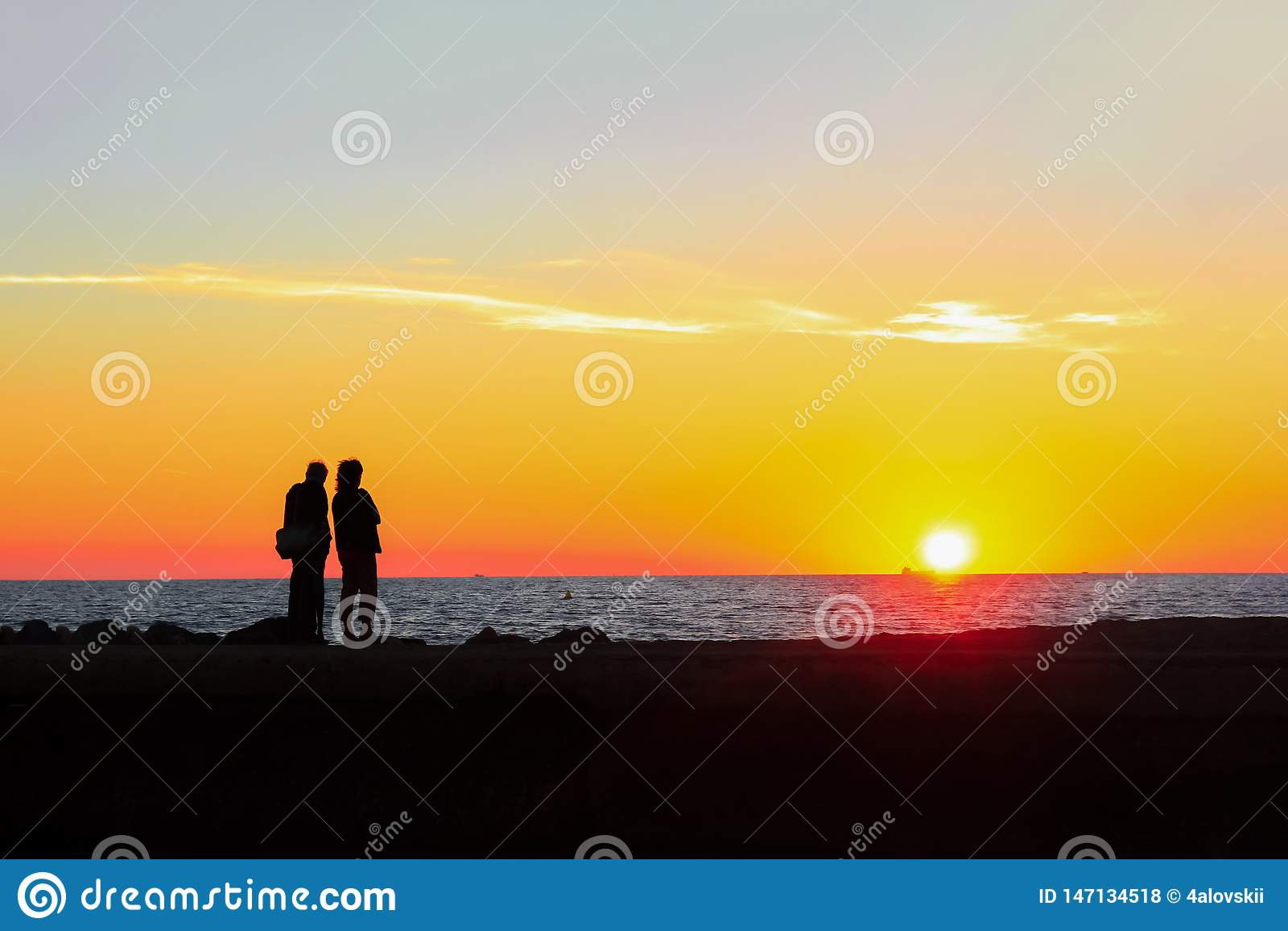 Mann und Frau bewundern den bunten Sonnenuntergang auf dem Strand