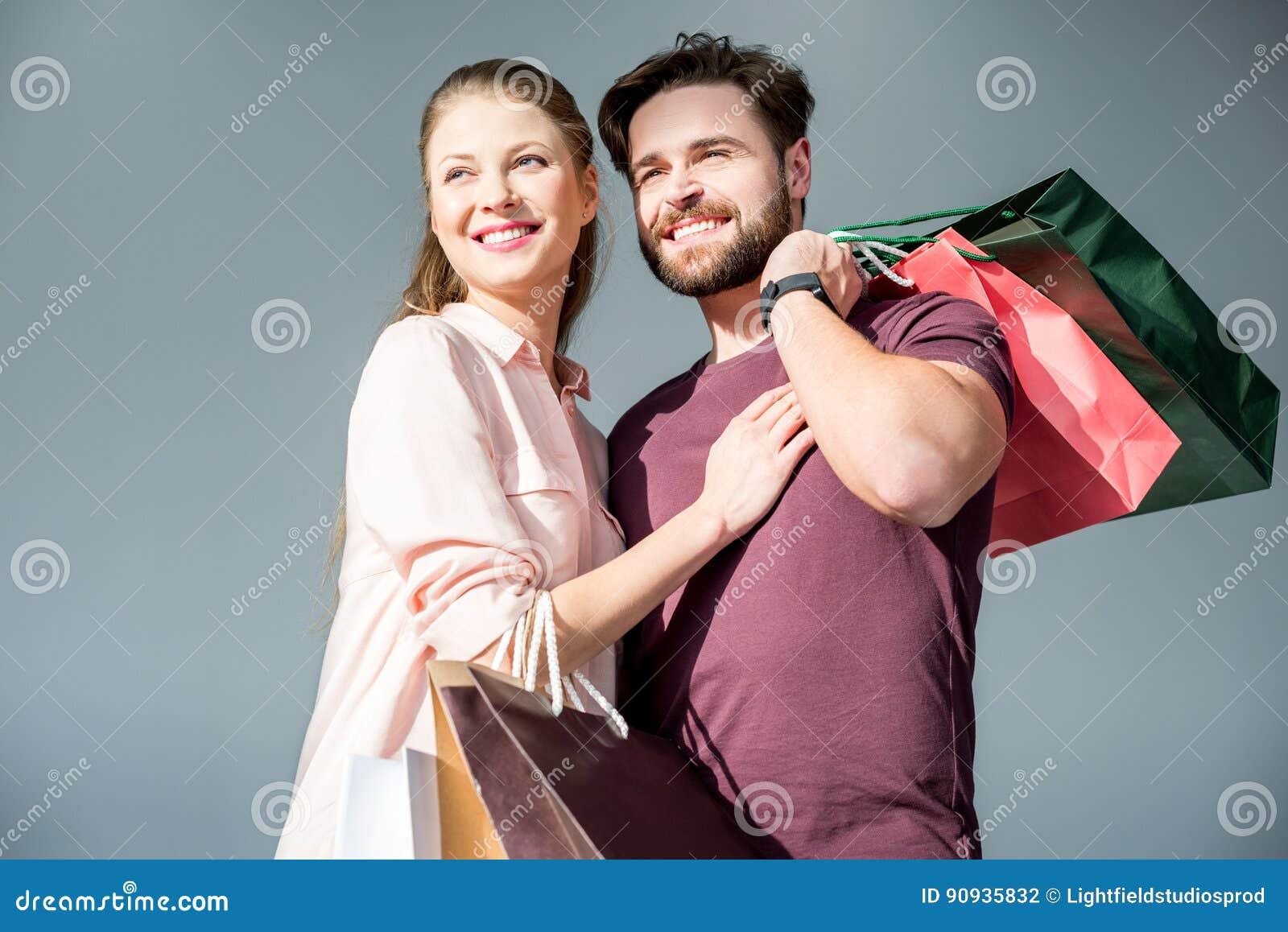 Mann und Frau, die mit Einkaufstaschen und dem Lächeln stehen