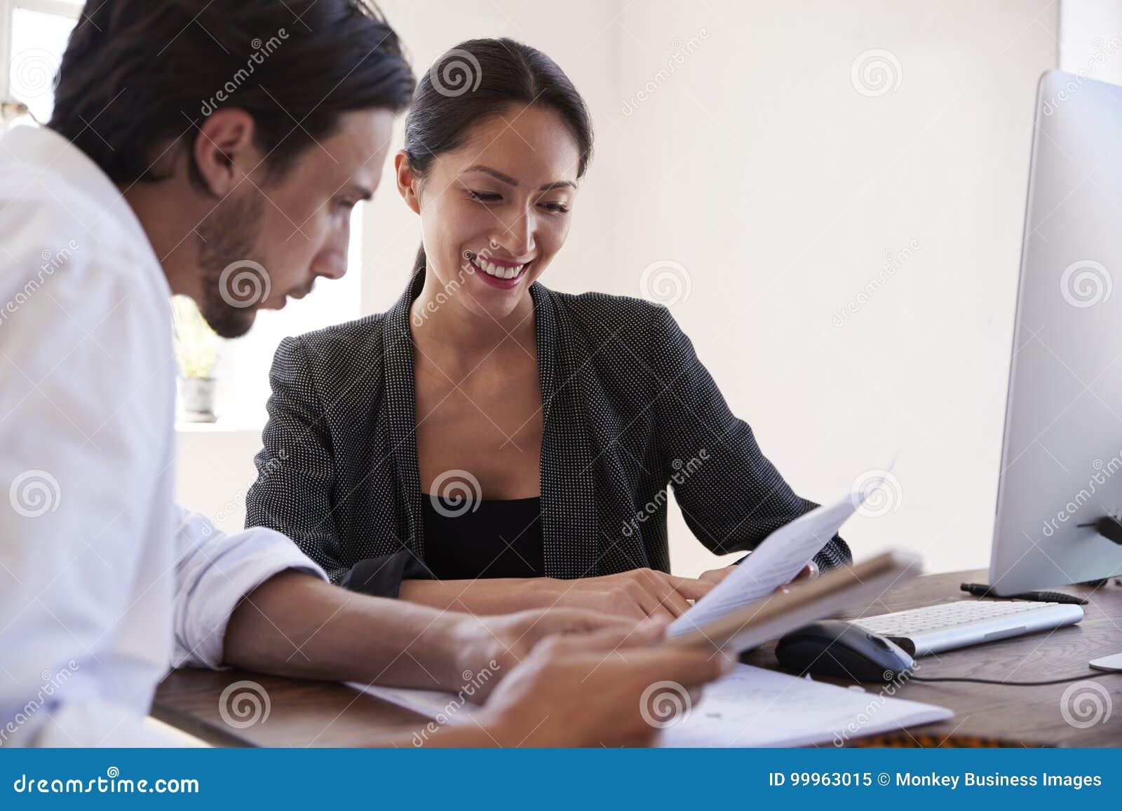 Mann und Frau, die oben Dokumente in einem Büro, Abschluss betrachten