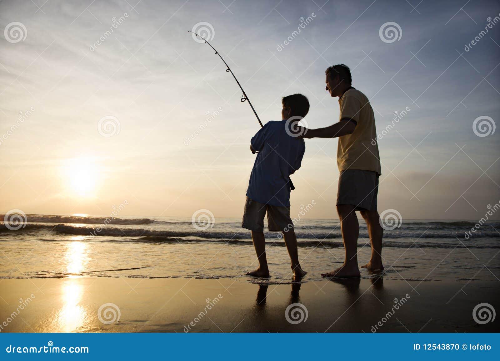 Mann und junges Jungenfischen in der Brandung
