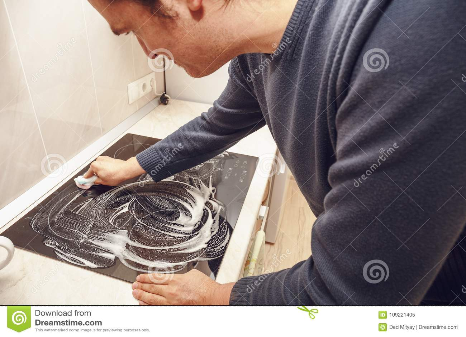 Mann wäscht modernen schwarzen elektrischen Ofen mit Seife Säubern Sie Haus
