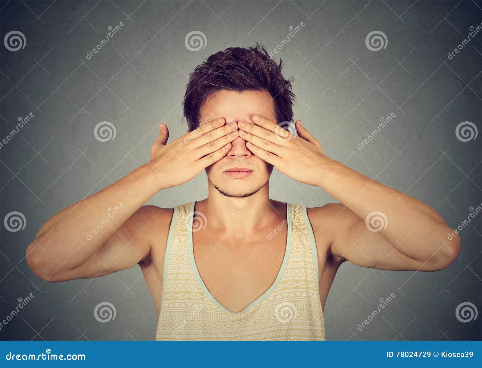 Mannbedeckungsaugen mit Handneigung sehen und verstecken sich