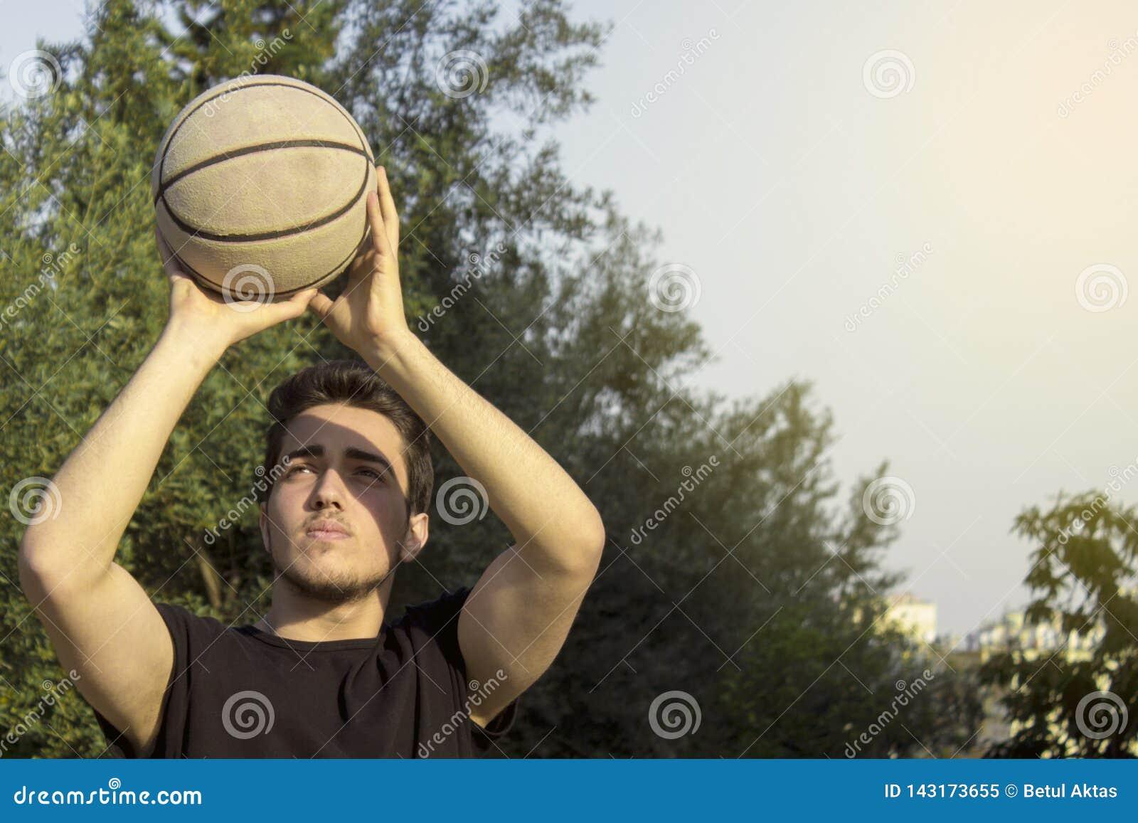 Mannelijk speelbasketbal openlucht
