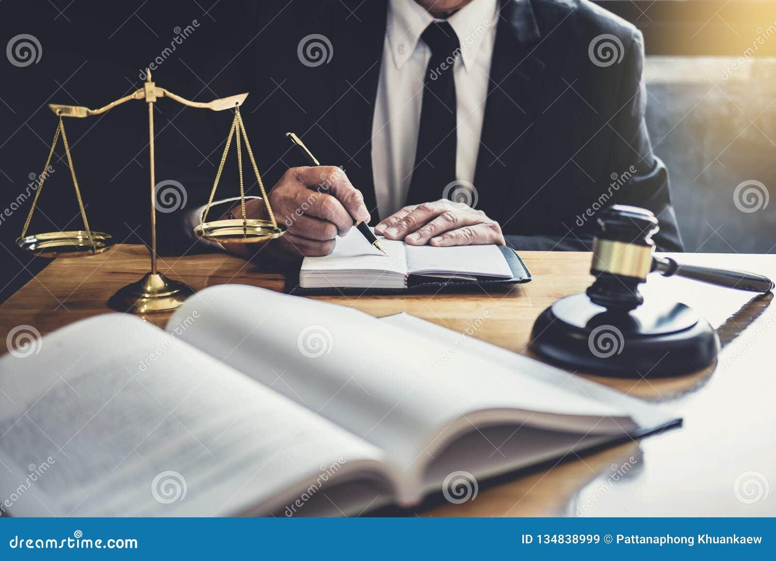 Mannelijke advocaat of rechter die met contractdocumenten, Wetsboeken en houten hamer aan lijst in rechtszaal, Rechtvaardigheidsa