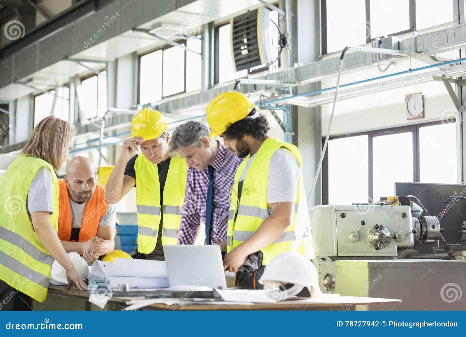 Mannelijke architect en handarbeiders die over blauwdrukken in de industrie bespreken