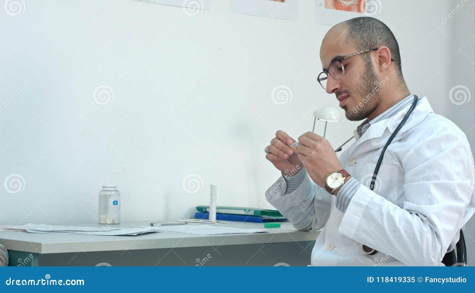Mannelijke arts die de temperatuur controleren op thermometer en medische vorm invullen
