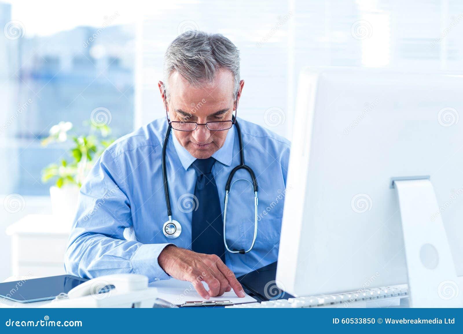 Mannelijke arts die document in het ziekenhuis onderzoeken