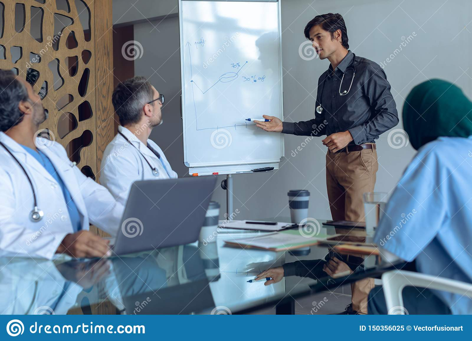 Mannelijke arts die over tikgrafiek in vergadering bij het ziekenhuis verklaren