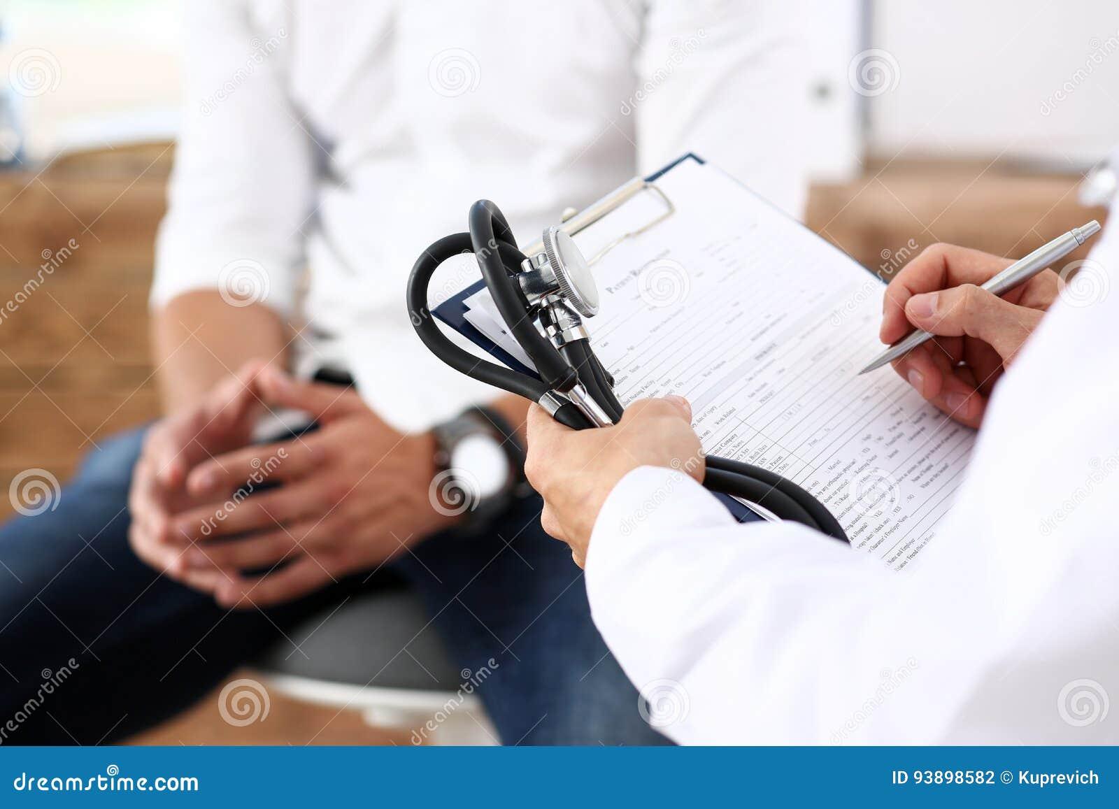 Mannelijke de greep zilveren pen die van de artsenhand geduldige geschiedenislijst vullen