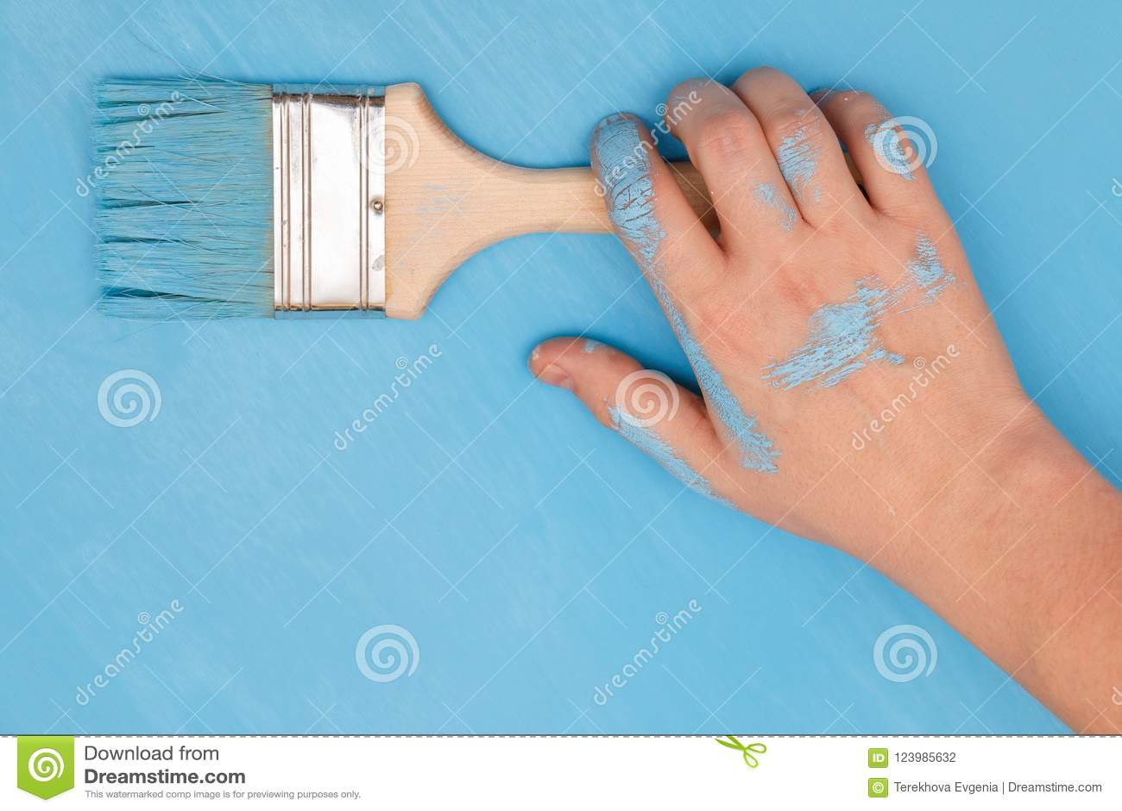 Mannelijke die hand in verf wordt behandeld, die een verfborstel houden