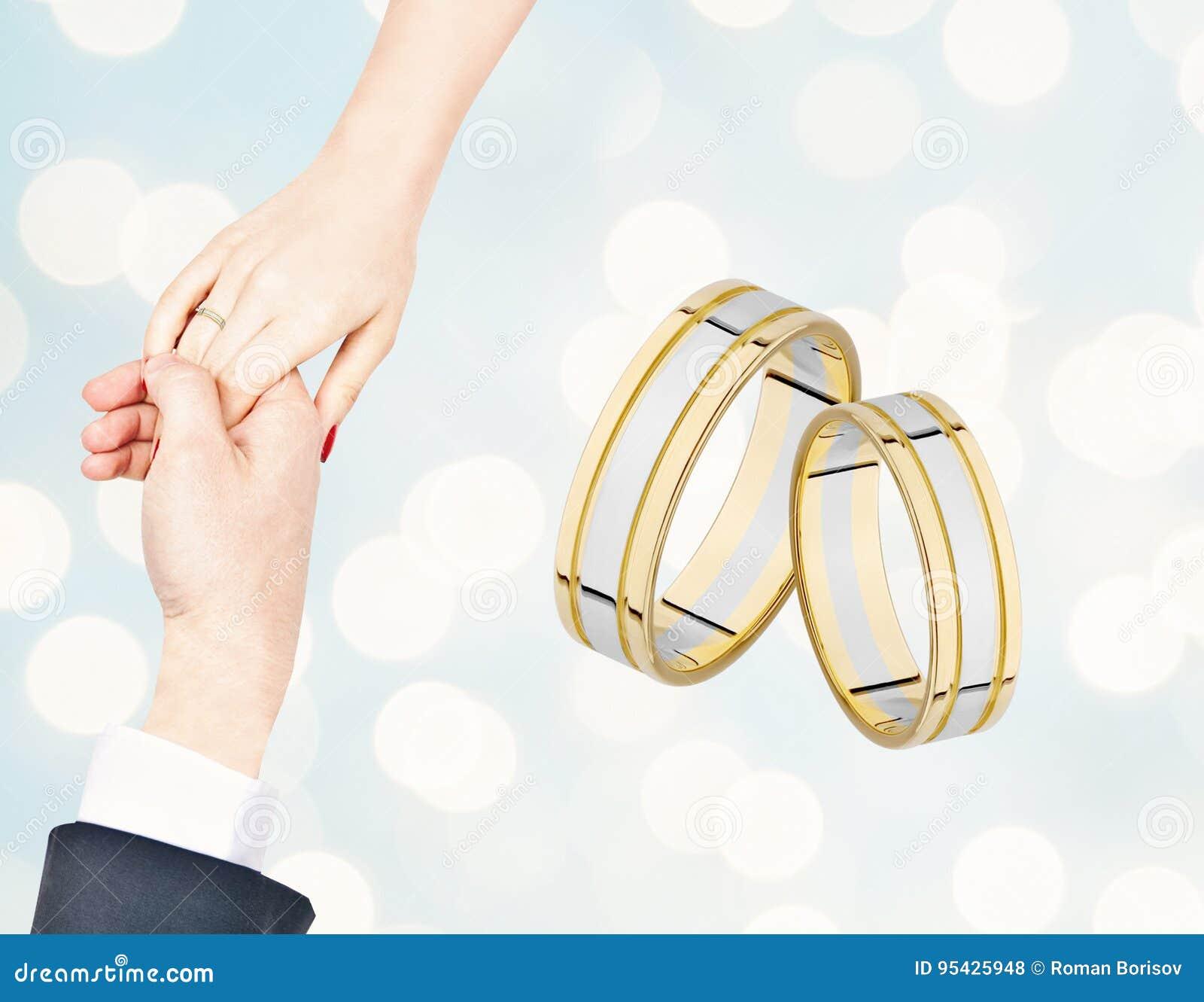 Mannelijke en vrouwelijke hand met een trouwring plaats voor exemplaarruimte