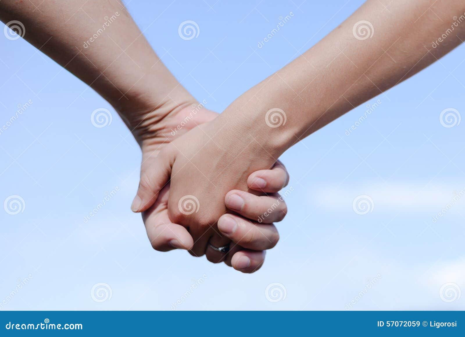 Mannelijke en vrouwelijke holdingshanden in openlucht over een blauw