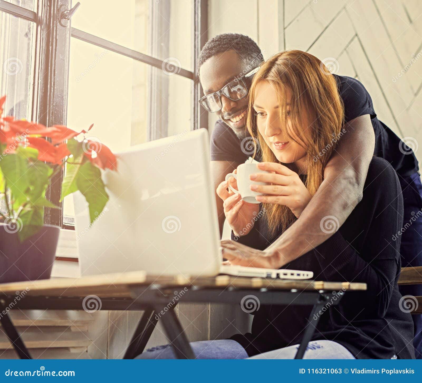 Mannelijke en vrouwelijke student die laptop met behulp van