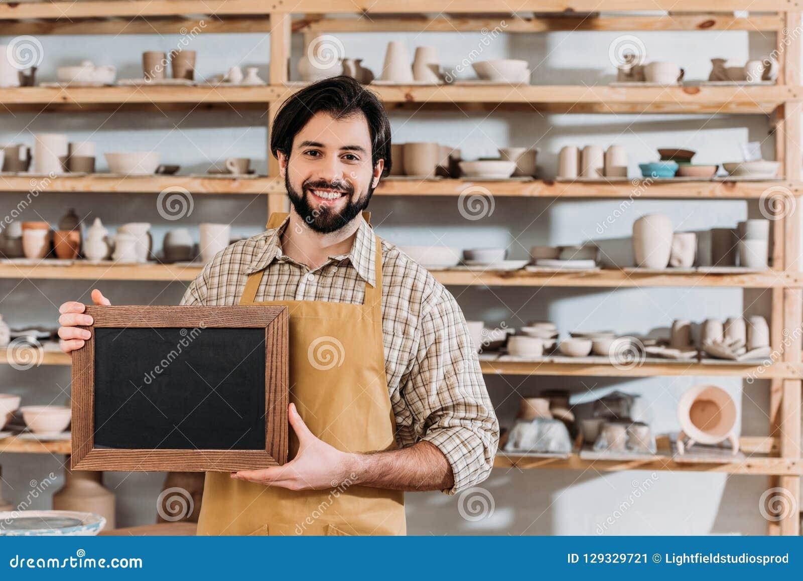 Mannelijke gebaarde eigenaar met bord in aardewerkworkshop
