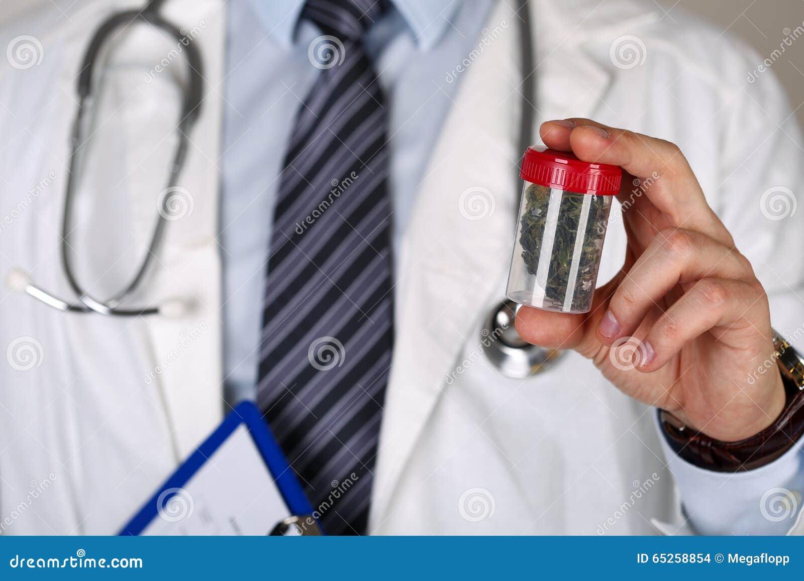 Mannelijke geneeskunde artsenhand die in hand medische marihuana houden