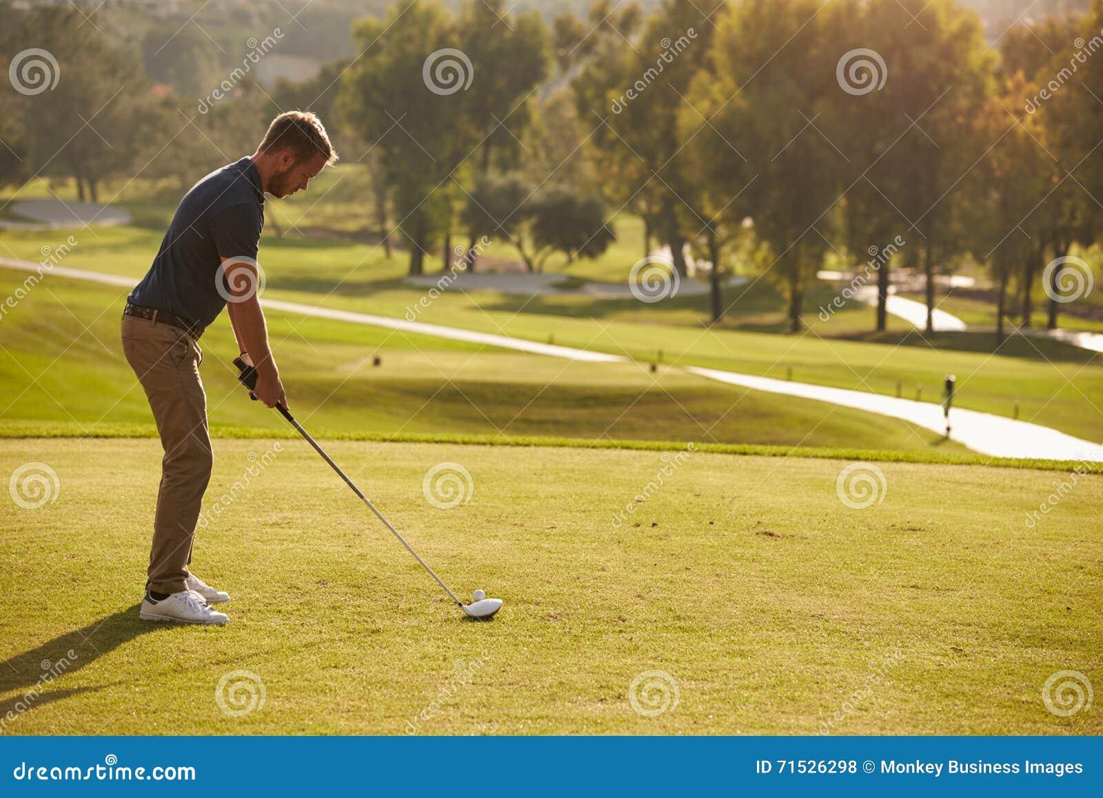 Mannelijke Golfspeler die die T-stuk opstellen op Golfcursus wordt geschoten