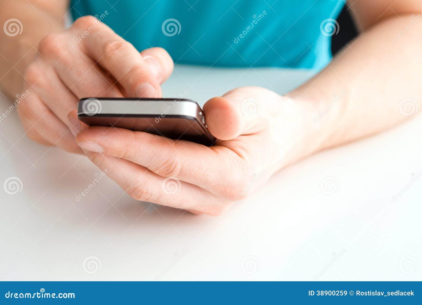 Mannelijke hand die een cel telefoon en het schrijven houden