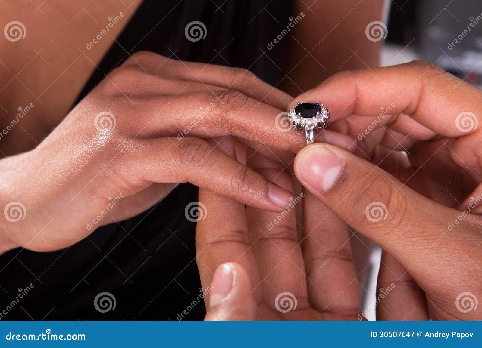 Mannelijke Hand die Ring Into opnemen een Vinger