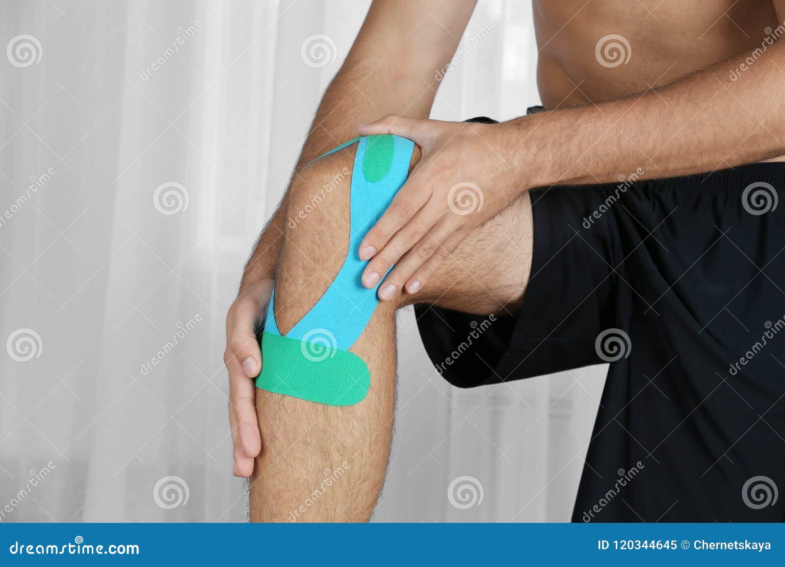 Mannelijke knie met toegepaste fysioband, binnen