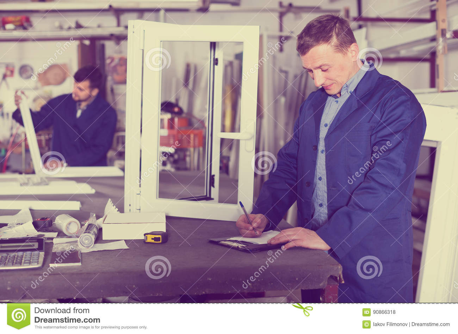 Mannelijke landmeter op middelbare leeftijd in overtrek die met documenten werken bij
