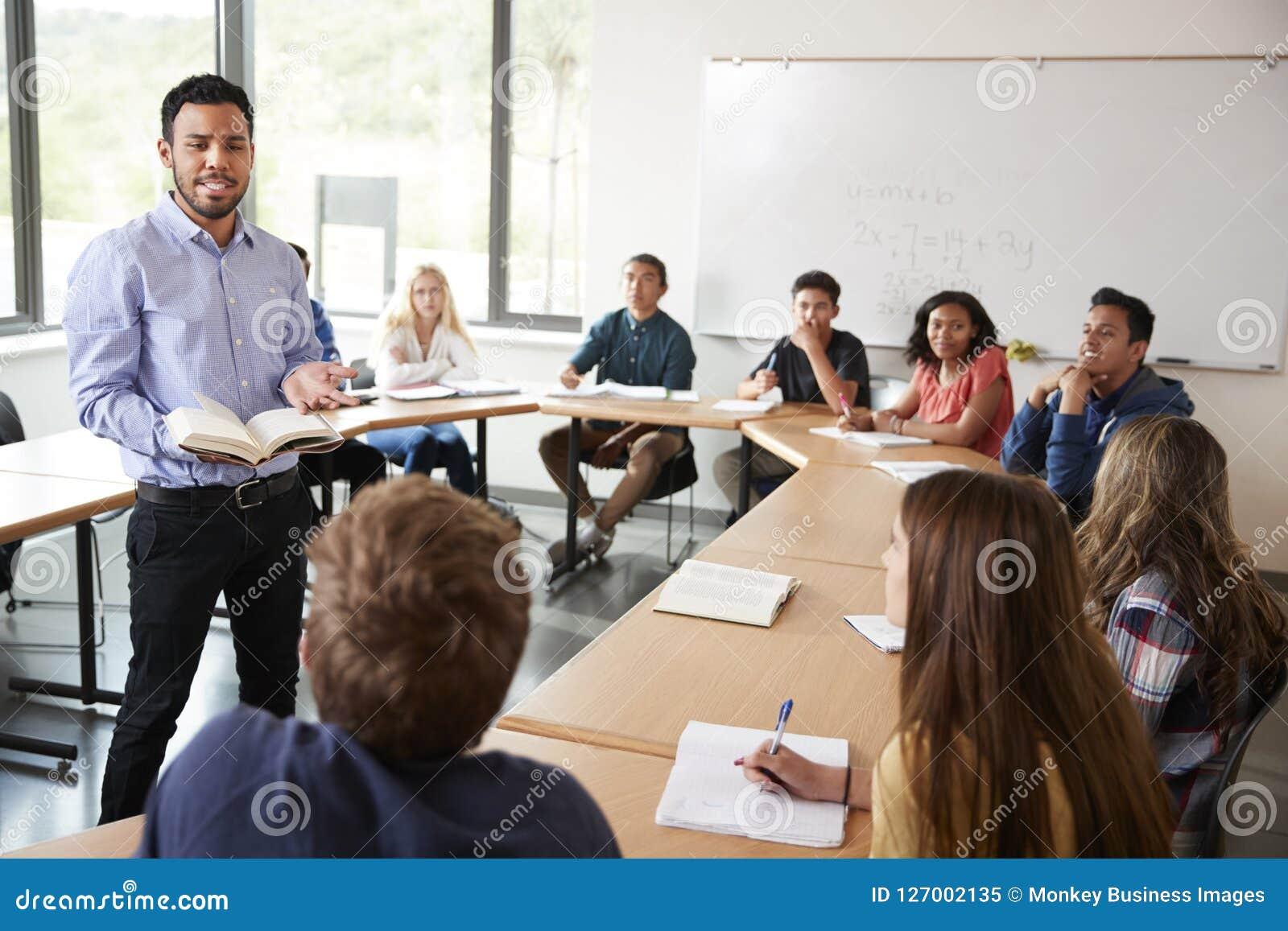 Mannelijke Middelbare schoolprivé-leraar With Pupils Sitting bij de Wiskundeklasse van het Lijstonderwijs