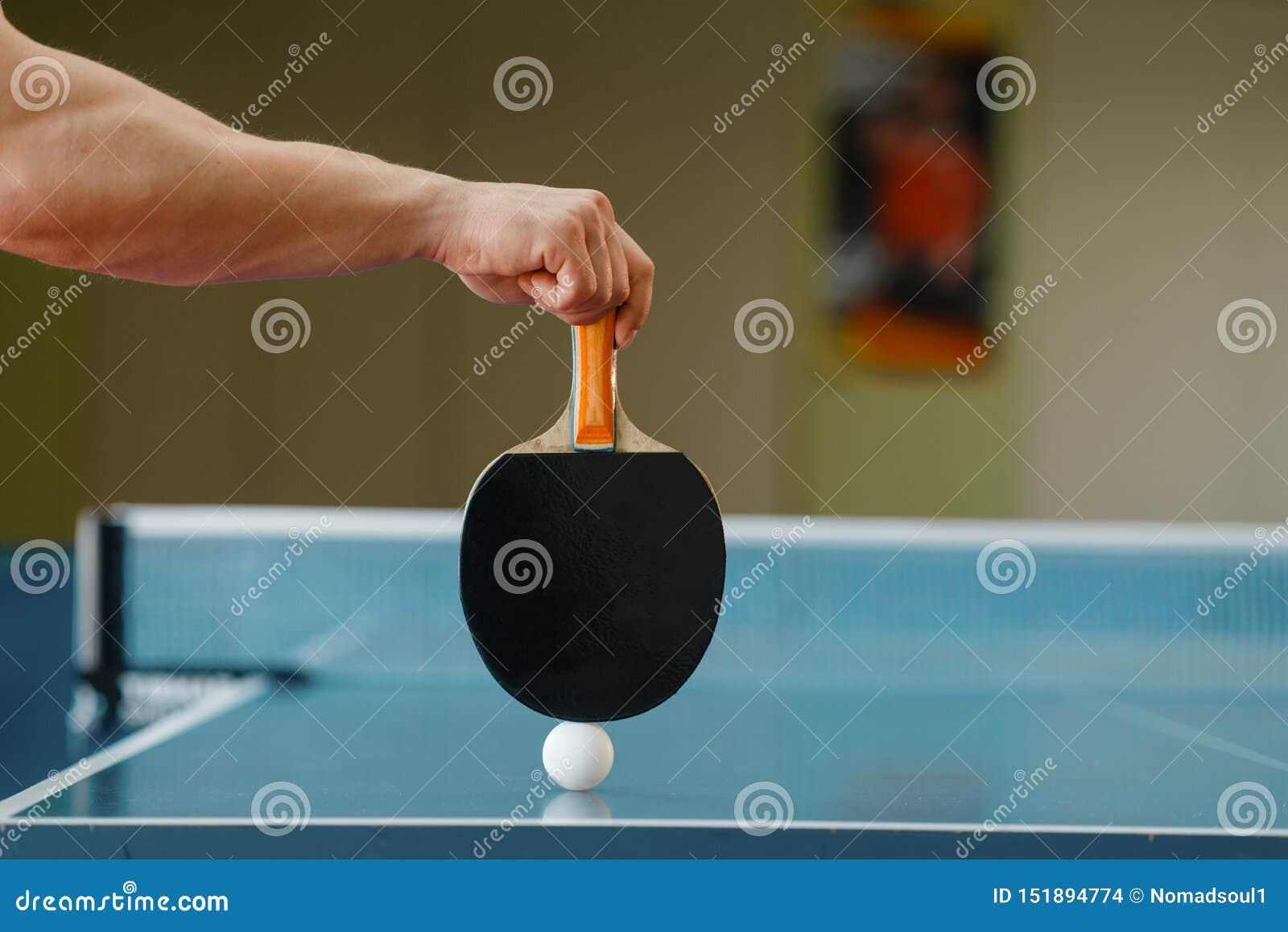 Mannelijke persoonshand met racket en pingpongbal