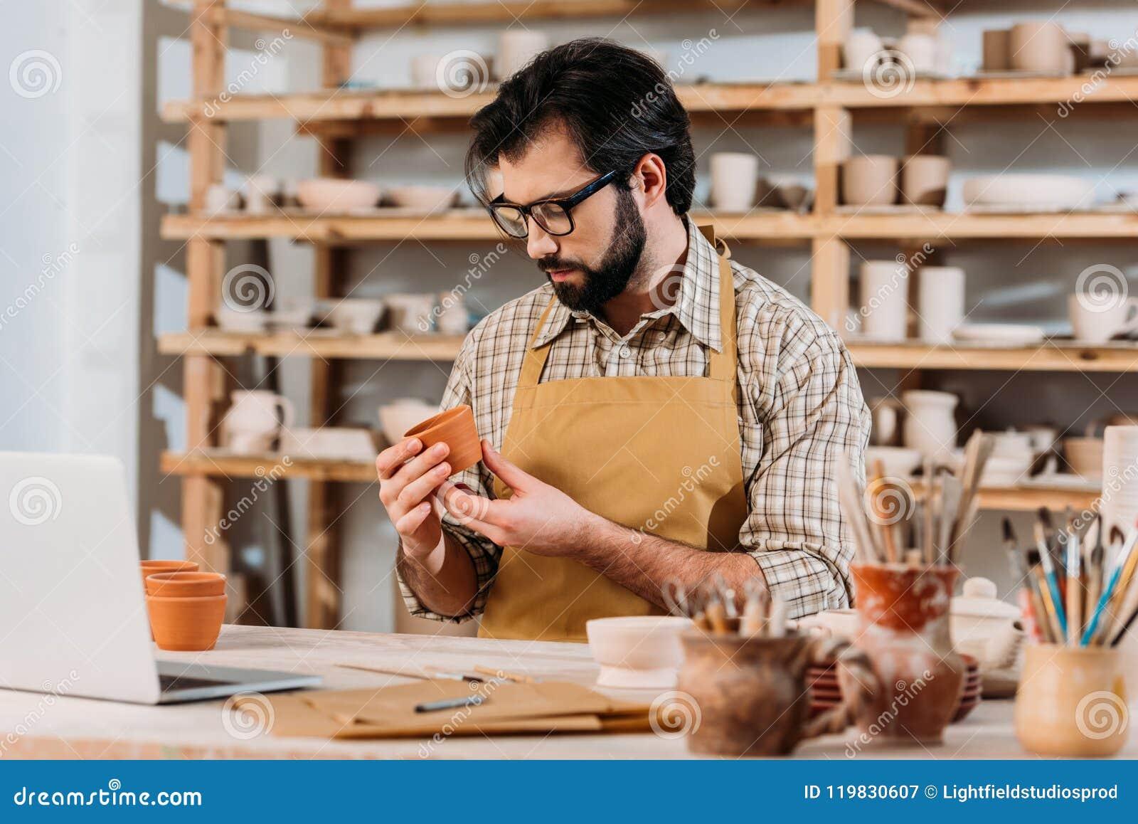 Mannelijke pottenbakker die in schort weinig bekijken