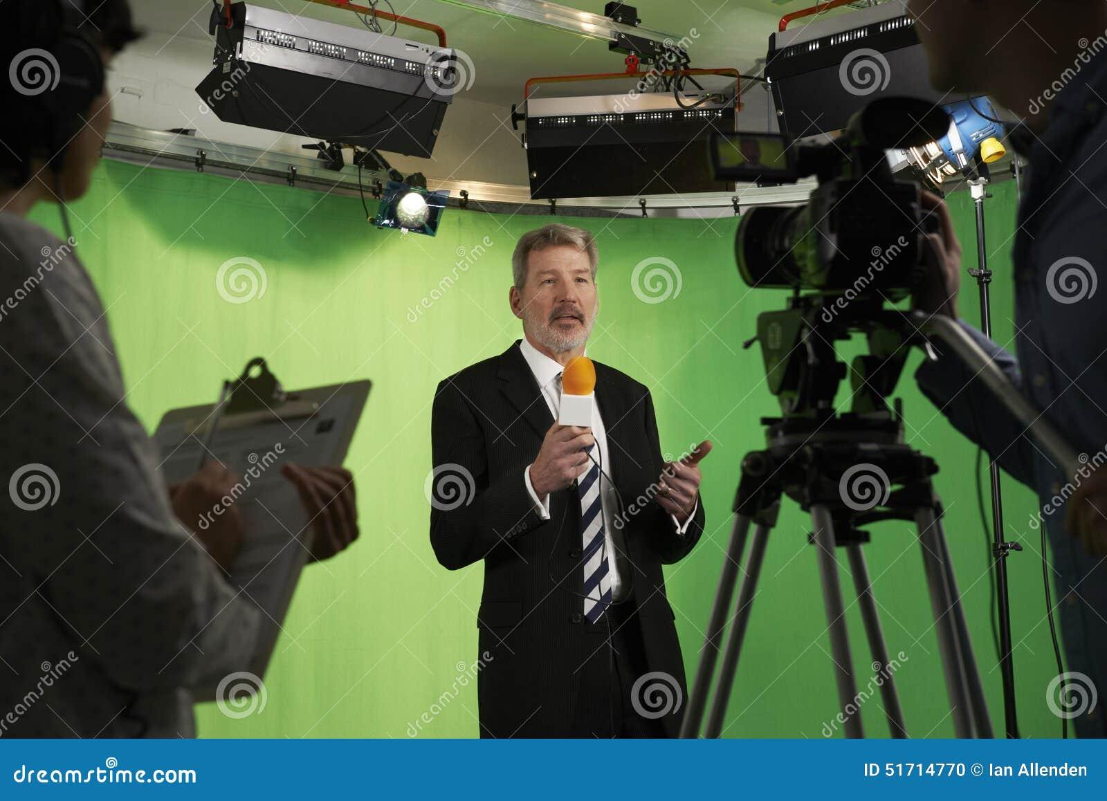 Mannelijke Presentator In Television Studio met Bemanning in Voorgrond