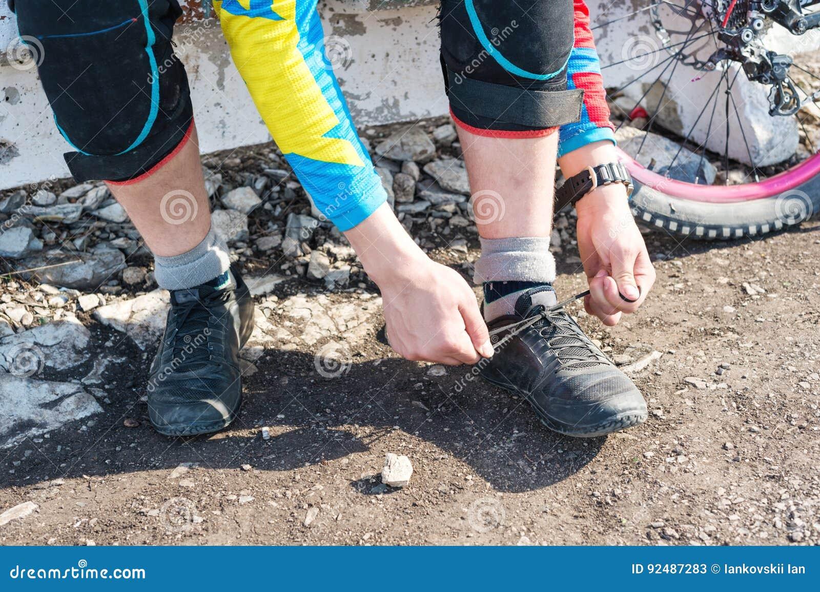 Mannelijke raceauto mtb fietser die voor ras bindende schoenveters voorbereidingen treffen