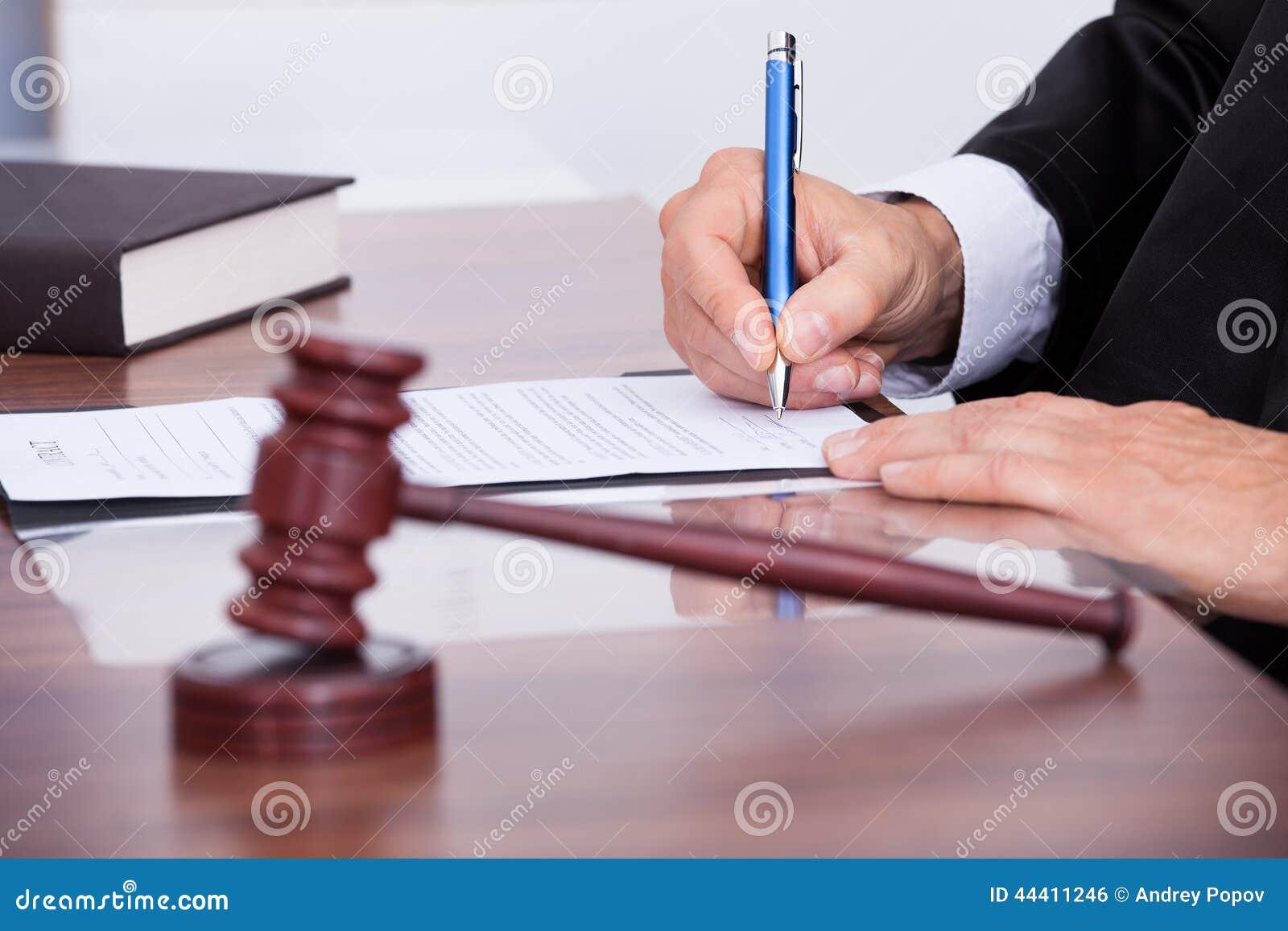 Mannelijke rechter die op papier schrijven
